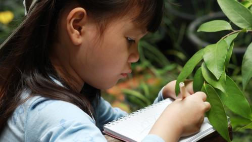 girl in front of plant taking notes