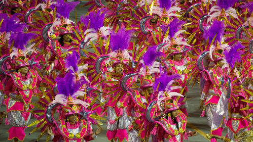 A group of samba dancers in bright red and purple costumes in Sao Paolo, Brazil, during Carival in February 2020