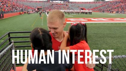 Rutgers cheerleader Andrew Geldreich hugs his deaf sisters
