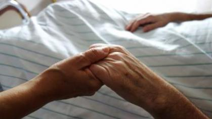 Holding a loved one's hand at a hospital bed