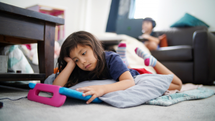 little girl laying on floor looking frutrated at her book
