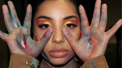 MGSA dance student Cassidy Rivas, posing with colorful paint on her face and hands