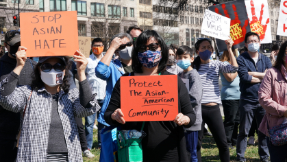 protesters holding signs of support for the Asiam American community
