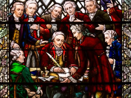 Stained glass window depicting the signing the Queen's College charter