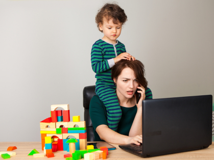 Mom working with child on her shoulders.