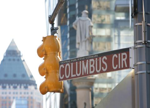 Columbus Circle street sign with statue of Christoper Columbus in the background