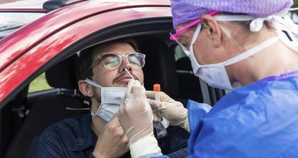 A health care worker at a drive-through testing center uses a nasal swab to test a patient for COVID-19