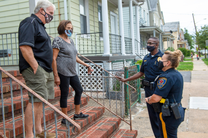 Officer Marlise Correa and Sergeant Bryant Myers, members of the  Rutgers University Police Department, talk with New Brunswick residents Mark and Joan Lomery