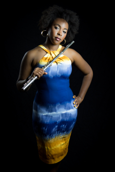 Adrienne Baker in a blue and yellow dress, holding a flute.